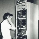 Operador de áudio em processo de gravação, com fitas de rolo.